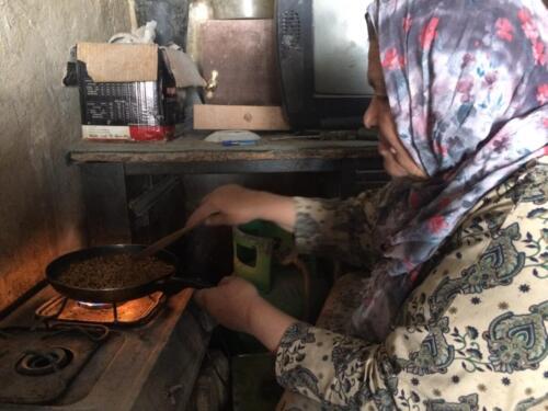 Aysheh A mills a customer's fresh herbs at her Baqa'a mill