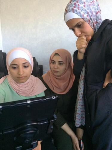 Students Afnan, Duaa and Shatha review their film footage